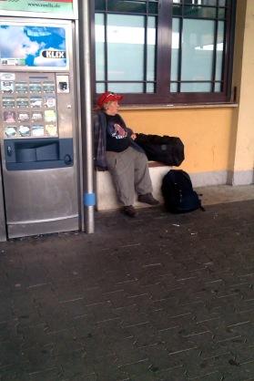 Sitzende Frau an einem Bahnhof